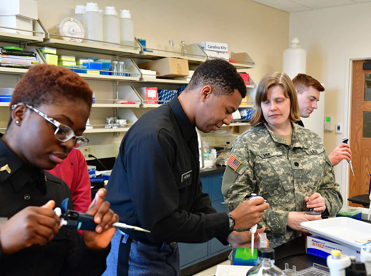 Two cadets demonstrate before a professor in a lab
