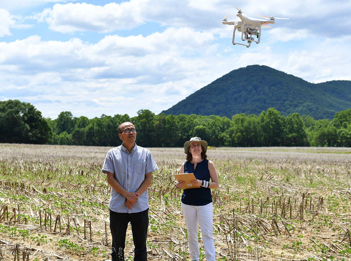 A man and woman stand in a field looking at a drone